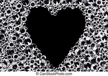 Hundreds of imitation diamonds on a black background with a heart shaped space in the middle.