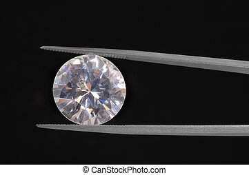 Diamond held by a gem tweezer shot on black