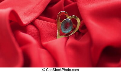 Diamond on heart shape ring on red satin