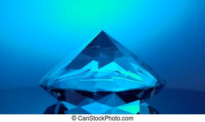 Diamond rotating at its point reflects blue light -...