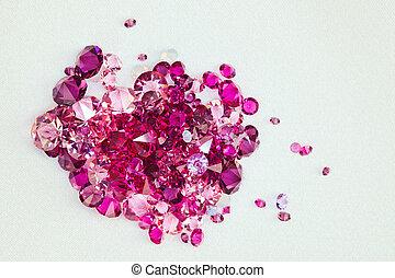 Diamond (ruby) stones heap over cream silk cloth background