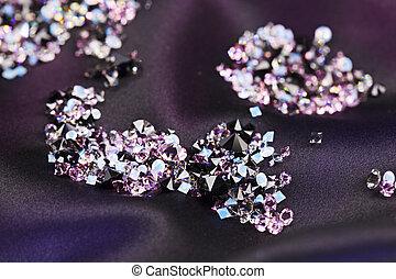 Diamond (small purple jewel) stones heap over black silk cloth background