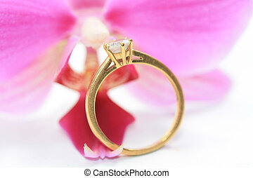 diamond solitaire engagement ring in front of orchid