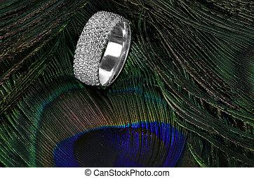 Diamond wedding ring on feathers