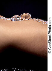 Diamonds on the stomach of a woman against a black background.