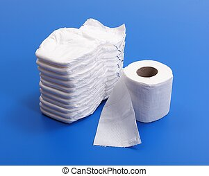 Stack of white diapers beside of toilet paper roll