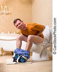 Diarrhea problem, man sitting on toilet bowl