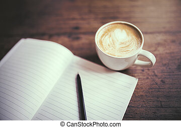 Diary with pen and cup of coffee on a wooden table
