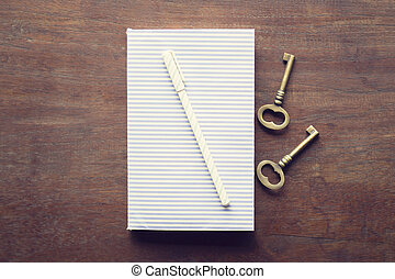 Diary with pen and keys on a wooden table