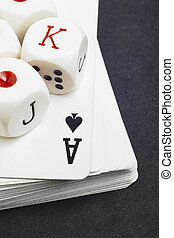 Dice and cards poker game over a black background
