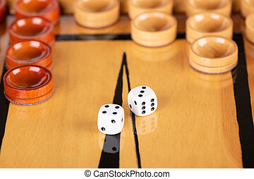 Dice and checkers on a wooden backgammon board.
