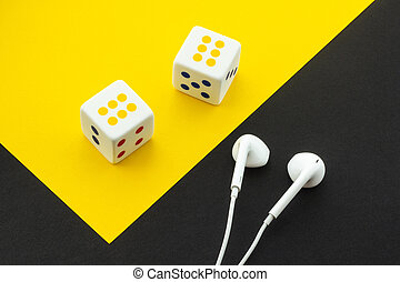 Dice and headphones on a black and yellow background