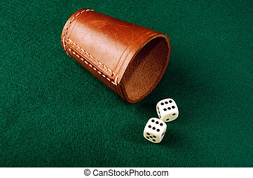 dice cup - dices and leather a cup on green cloth