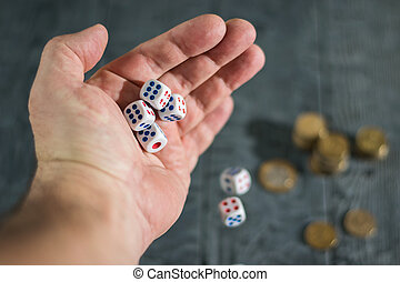 Dice fall out of the hand of a man on a black wooden table with Golden coins.