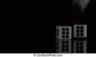 Dice fall slow motion on the black background.