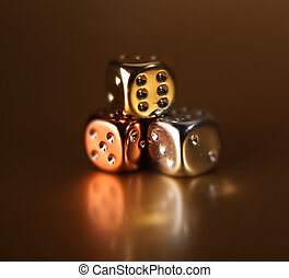 stack of dice or die on bronze background with reflection. numbers on cube game equipment. symbol of risk, gambling or chance