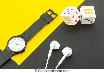 Dice, headphones and a clock on the background