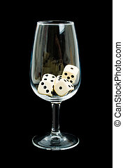 Dice in a wine glass over black background