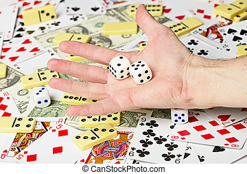 Dice on palm on the background cards and money