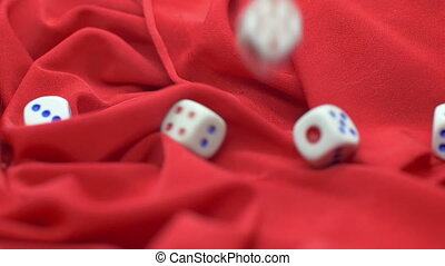 Dice rolling on red satin slow motion