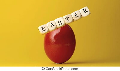 Dice spelling out easter falling in front of red egg in slow...