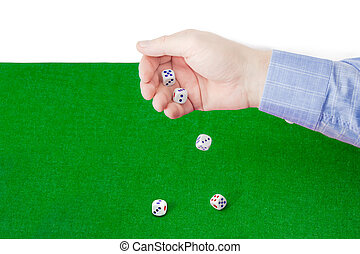 Dice thrown from male hand on table with green cloth