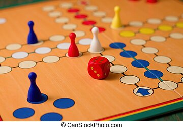 Horizontal photo of Dice with number six up among figurines on ludo board placed on green board
