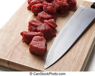 Diced chuck steak on chopping board with knife