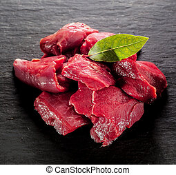 Uncooked lean healthy diced deer steak for a venison goulash with a bay leaf on a textured dark background, close up high angle