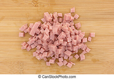 Diced ham on a wood cutting board
