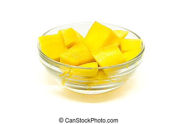 Diced mango cubes placed and served on a glass bowl isolated on a white background