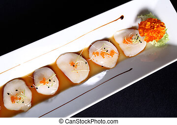 diced scallops with sauce on rectangular white plate, black ...