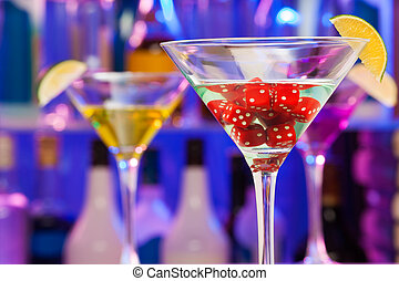 Dices in cocktail glass with lime and bar on back