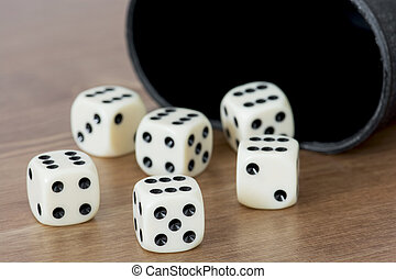 Dices with cup on the table.