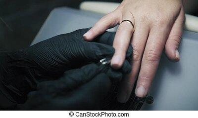 dichtbegroeid boven, schoonheidspecialist, in, black , handschoenen, holle weg, de, nagelriem, door, metaal, instrumet, in, spijker, salon., spijker, meester, voorzichtig, en, nauwkeurig, het verwijderen, opperhuid, met, nagelknippers
