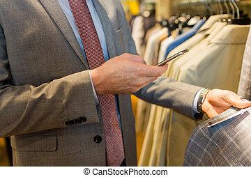 dichtbegroeid boven, van, man, met, smartphone, op, de opslag van de kleding