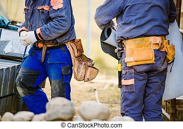 dichtbegroeid boven, van, twee, bouwpersoneel, met, werktuig, zakken