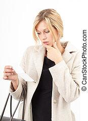 Die Rechnung - Junge Frau betrachtet erschrocken eine...