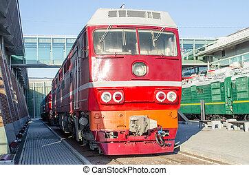 Diesel locomotive on the platform of the railway station.