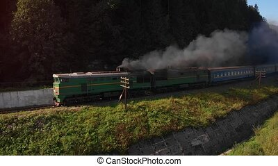 Tandem diesel locomotives haul a passenger train along the course of the Prut River and throught he Ukrainian Carpathian Mountains.
