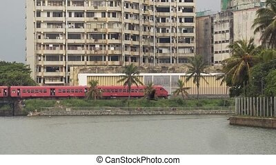 Diesel Passenger train passing through urban Colombo, Sri...