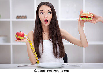 Diet. Beautiful Young Woman choosing between Fruits and Junk food