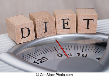 Diet Blocks Arranged On Weight Scale - Closeup of Diet...