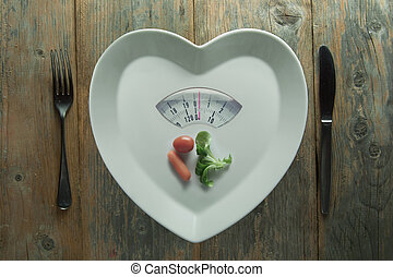 Diet concept - Heart shape plate with weighing scales and a...