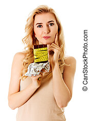 Diet concept - woman holding bar of chocolate tied with measure tape