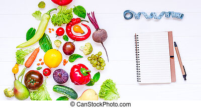 Diet, detox planning new year concept - fresh vegetables and fruits in the form of christmas tree. Notebook, measure tape on the white wooden background. Top view. Selective focus. space for text.