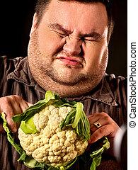Diet fat man eating healthy food. Healthy breakfast vegetables cauliflower.