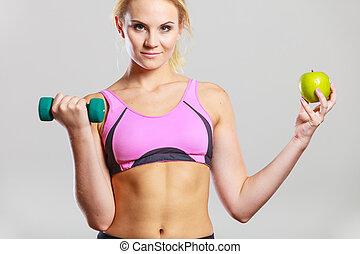 Diet fit body. Girl holds dumbbells and apple fruit