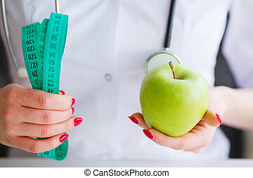 Diet. Fitness and healthy food diet concept. Balanced diet with vegetables. Portrait of cheerful doctor nutritionist measuring green apple in her office. Concept of natural food and healthy lifestyle