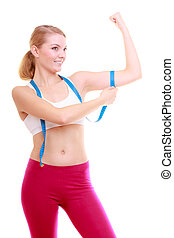 Diet. Fitness woman fit girl with measure tape measuring her biceps